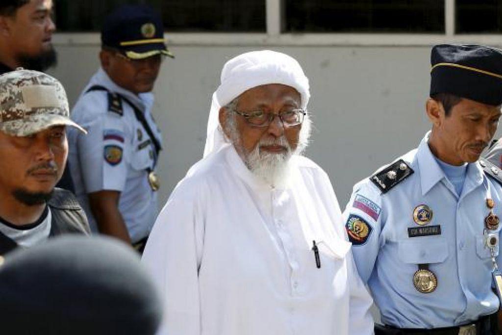 KAWALAN KETAT: Abu Bakar Bashir (berjubah putih) dikawal ketat anggota keselamatan Indonesian yang menggiringnya ke Mahkamah Cilacap, Jawa Tengah, bagi semakan kehakiman semalam. Abu Bakar dihukum penjara 15 tahun pada 2011. - Foto REUTERS