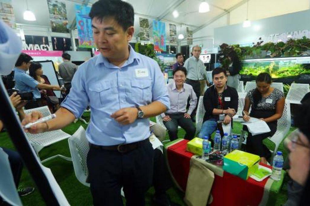 SERIKAN SEKITARAN: Menteri Pembangunan Negara, Encik Lawrence Wong (duduk, kiri), berkongsi pandangan dengan peserta lain dalam satu dialog mengenai 'Penghijauan Bandar Kita - Inovasi, Idea dan Huraian' bagi meninjau idea tentang bagaimana menjadikan Singapura sebuah negara lebih bersih, hijau dan bijak. - Foto ZAOBAO