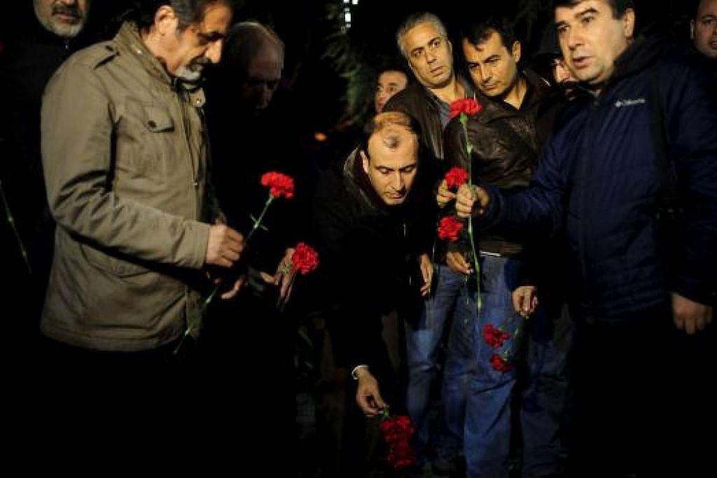 LUAHKAN SIMPATI: Anggota Dewan Perubatan Istanbul meletakkan kuntuman bunga dekat tapak serangan bom di pusat bersejarah Sultanahmet, kelmarin. - Foto REUTERS