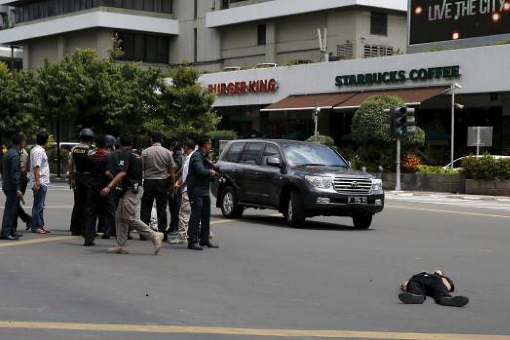 Sekujur tubuh terbaring di jalan sedang pegawai polis Indonesia yang bersenjata berlindung di belakang sebuah kereta di Jakarta pada Khamis, 14 Jan. Gambar REUTERS
