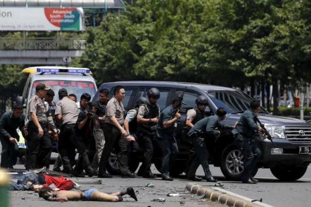 Sekujur tubuh tergelimpang sedang pegawai polis berhadapan dengan penyerang yang disyaki pengganas dalam kejadian letupan dan tembak-menambak di Jakarta pada Khamis, 14 Januari. Gambar REUTERS