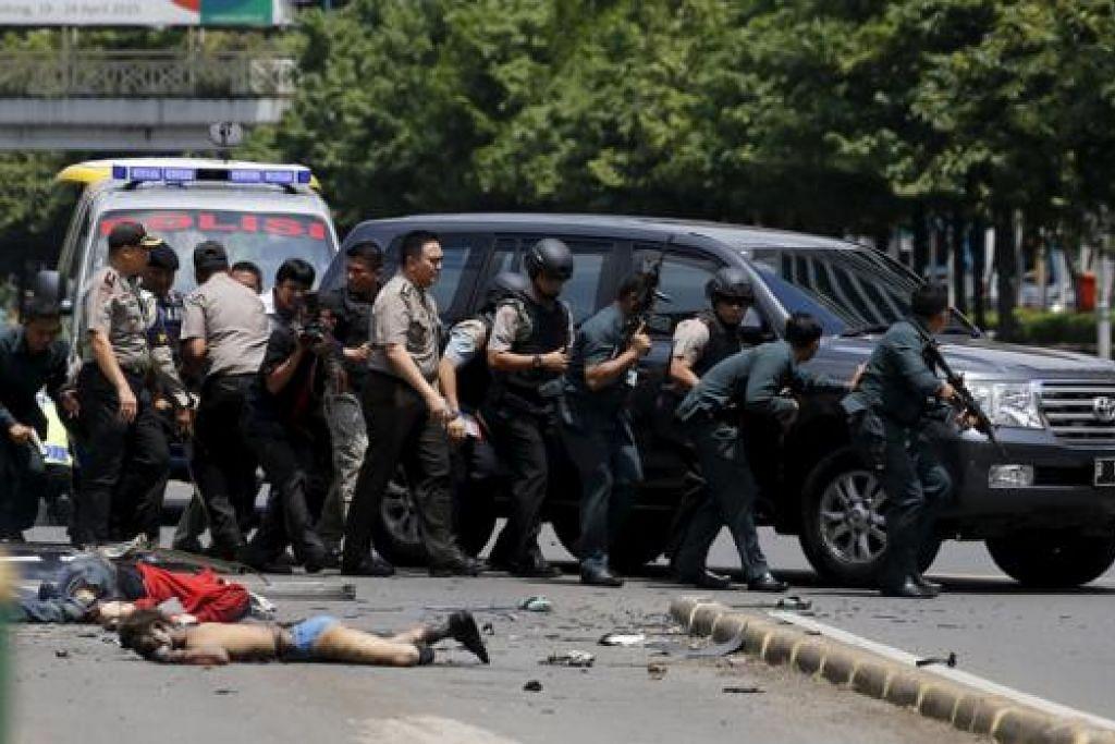 TANGKIS SERANGAN: Polis Indonesia berlindung di belakang kereta sewaktu berlakunya serangan nekad di Jakarta semalam. - Foto REUTERS