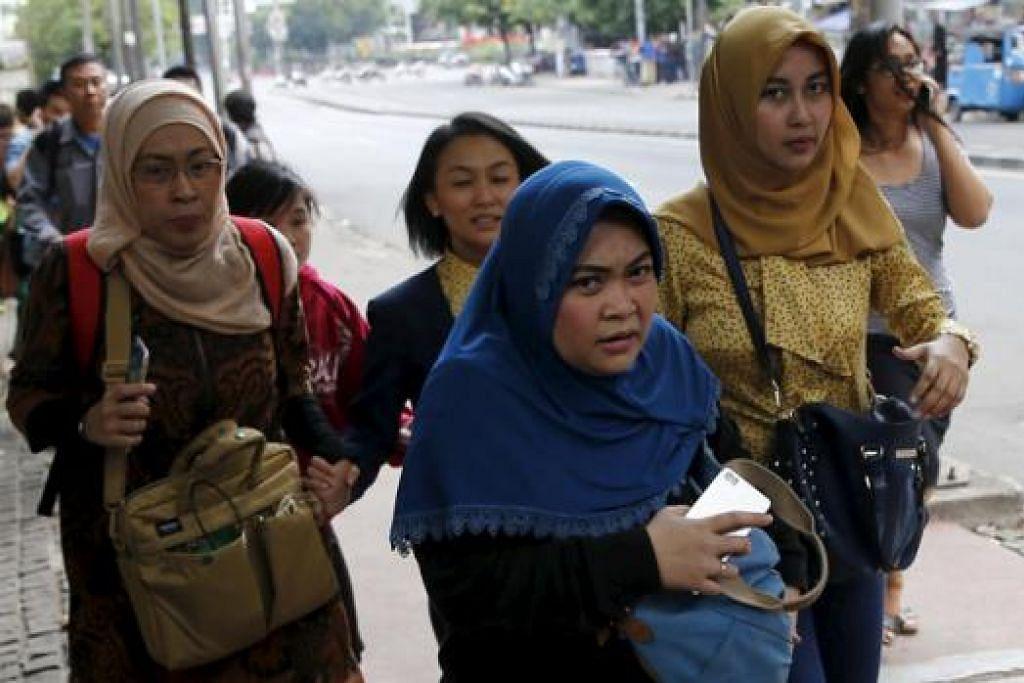 SELAMATKAN DIRI: Pekerja Indonesia melarikan diri daripada pejabat di kawasan perniagaan Thamrin, Jakarta, semalam selepas berlaku serangan bom. - Foto REUTERS