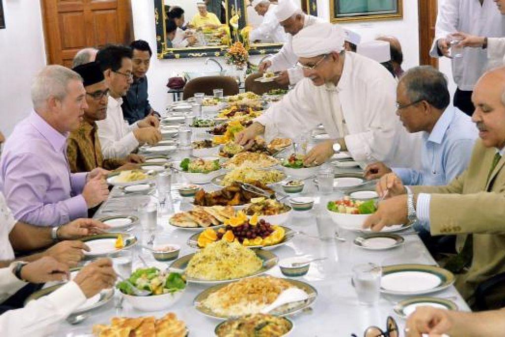 SEBELUM KE PARLIMEN: Encik Masagos (kanan) sempat menjamu selera bersaman beberapa kenalan dan jemaah termasuk (dua dari kanan) Habib Hassan, (dari kiri) Encik Kirk Wagar dan Encik Zainul Abidin. - Foto KHALID BABA