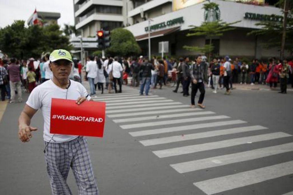 """MAHU TERUSKAN KEHIDUPAN SEPERTI BIASA: Seorang penduduk setempat memegang sepanduk yang bermaksud """"Kami tidak gentar"""" di jalan raya yang sibuk seperti biasa semalam di depan kafe Starbucks dekat pusat beli-belah Sarinah Mall, Jakarta, yang merupakan antara lokasi letupan kelmarin. - Foto REUTERS"""