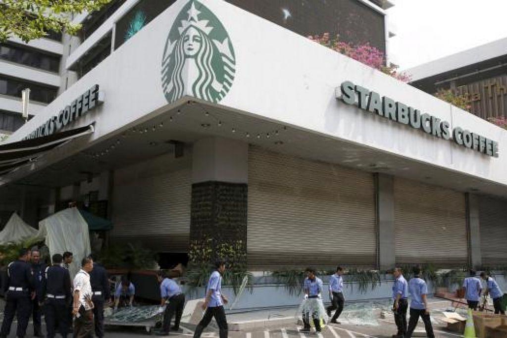BERSIHKAN KAWASAN: Pekerja membersihkan sekitar kawasan restoran Starbucks Coffee dekat tempat serangan militan yang membunuh tujuh orang termasuk lima anggota militan. - Foto REUTERS