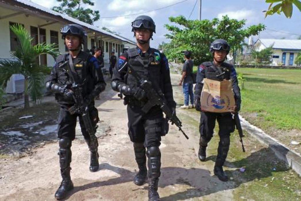 SALAH seorang daripada pegawai polis antipengganasan Indonesia membawa sebuah kotak yang diambil daripada kediaman seorang individu yang disyaki militan di Sampit, Kalimantan Tengah semalam. Individu itu dipercayai terlibat dalam serangan di Jakarta Khamis lepas. – Foto REUTERS