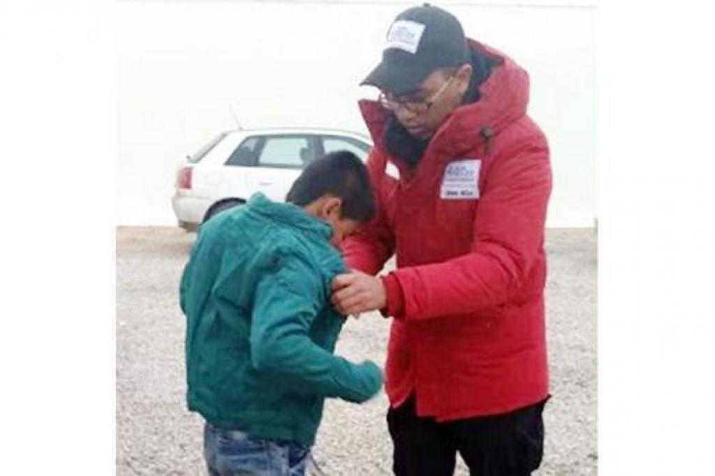 SESUAIKAN BANTUAN: Pengagihan bantuan pakaian musim sejuk agak rumit kerana setiap pelarian memerlukan saiz yang berbeza. Encik Shah dirakam sedang memastikan jaket yang dipakai budak lelaki itu sesuai pada tubuhnya.