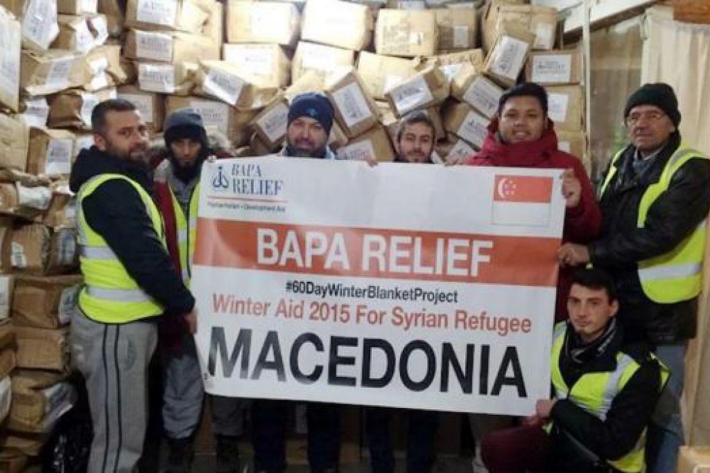 RAKAN KERJA: Bapa Relief bergambar dengan NGO Albania, Rahma Mercy, dan NGO Macedonia, Nun Kultura, dalam gudang menyimpan bantuan hasil derma rakyat Singapura. Gudang itu terletak di Skopje.