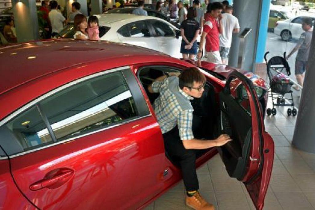 DIBANJIRI PENGUNJUNG: Ekoran penurunan harga COE kategori A, pusat membeli kereta dikunjungi ramai bakal pembeli yang berminat menggantikan kereta mereka yang kian usang. – Foto THE STRAITS TIMES