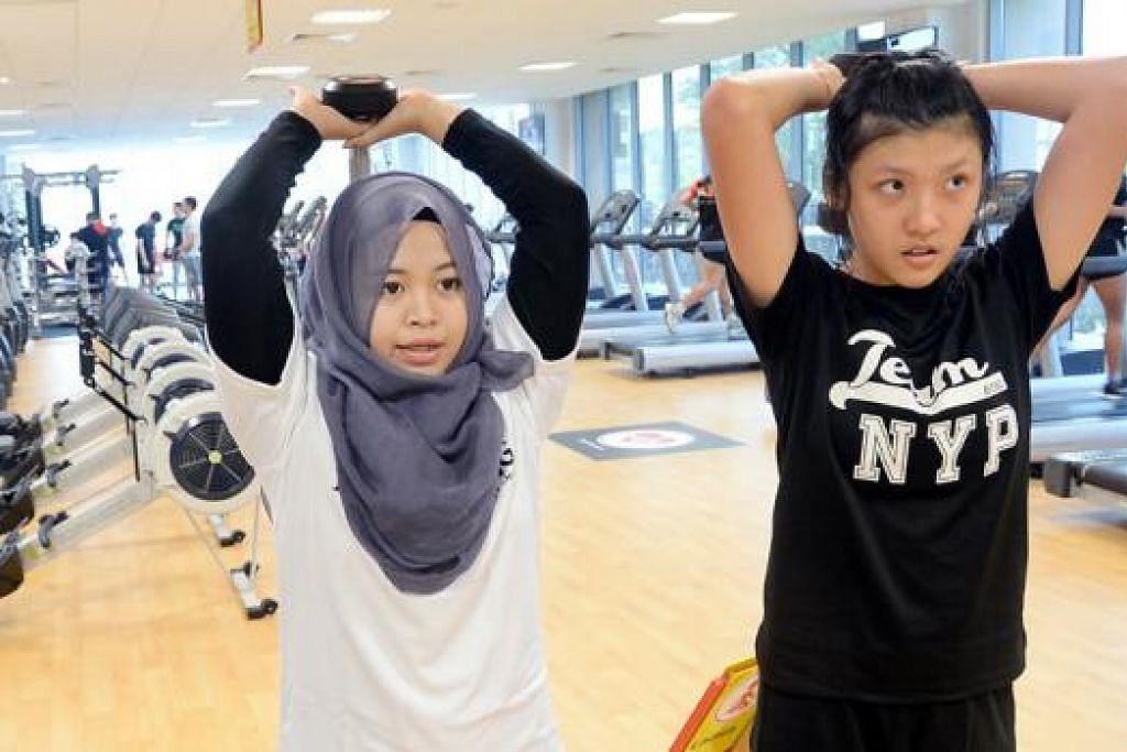 PUAS APABILA PELANGGAN PUAS: Cik Syafiqah (kiri) menunjukkan teknik betul kepada seorang pelanggan dalam sesi latihan jasmani di gimnasium. - Foto JOHARI RAHMAT