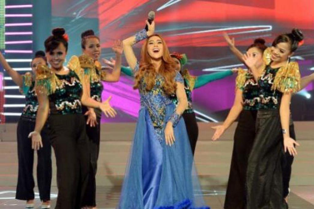 PERSEMBAHAN BERTENAGA: Penyanyi dangdut Indonesia, Cita Citata, menghiburkan peminat dalam Fiesta Pos T.K.I. kelmarin. Di kiri dan kanannya ialah penari terdiri daripada pembantu rumah dari Indonesia. - Foto TAUFIK A. KADER