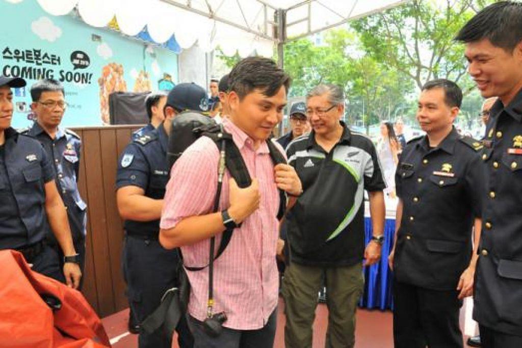 BERSIAP SEDIA: Encik Saktiandi mencuba peranti khas SCDF di Hari Bersiap Sedia bagi Kecemasan di Novena Square. - Foto PA