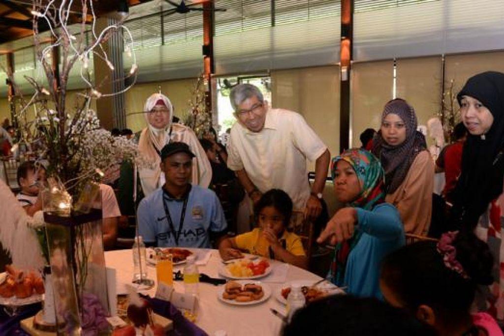 MENGENALI LEBIH DEKAT: Dr Yaacob Ibrahim sedang beramah mesra dengan keluarga angkat yang menghadiri majlis ulang tahun Vista Sakinah yang kelima, Sabtu lalu. - Foto TAUFIK A. KADER