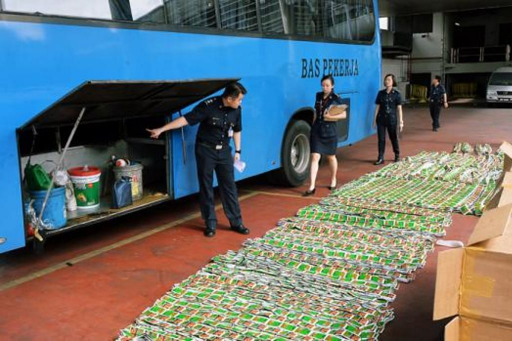 PATAHKAN PERCUBAAN SELUDUP: Pegawai ICA memeriksa sebuah bas pekerja yang cuba menyeludup tembakau tanpa cukai semalam. - Foto KHALID BABA