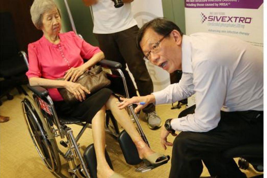 KESAN JANGKITAN MRSA: Pakar penyakit jangkitan, Dr Leong Hoe Nam, menunjukkan kesan MRSA yang dialami Cik Gan di kaki kirinya. - Foto THE STRAITS TIMES