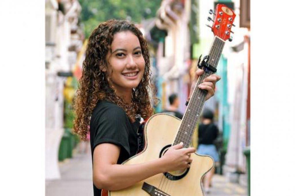 DEKATI BELIA: Petikan gitar pemuzik muda Mariam Bamadhaj telah memberinya peluang mendekati belia kurang bernasib baik ketika beliau menjalani latihan amali sebagai penyelaras projek belia di Persatuan Masyarakat Castlehaven di kawasan Camden, London. - Foto KHALID BABA
