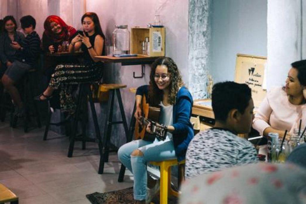MENDENDANG LAGU CIPTAAN: Mariam Bamadhaj sedang mempersembah empat lagu asli tulisan dan gubahannya di Kafe Wilder pada Jumaat lalu. - Foto ihsan MARIAM BAMADHAJ