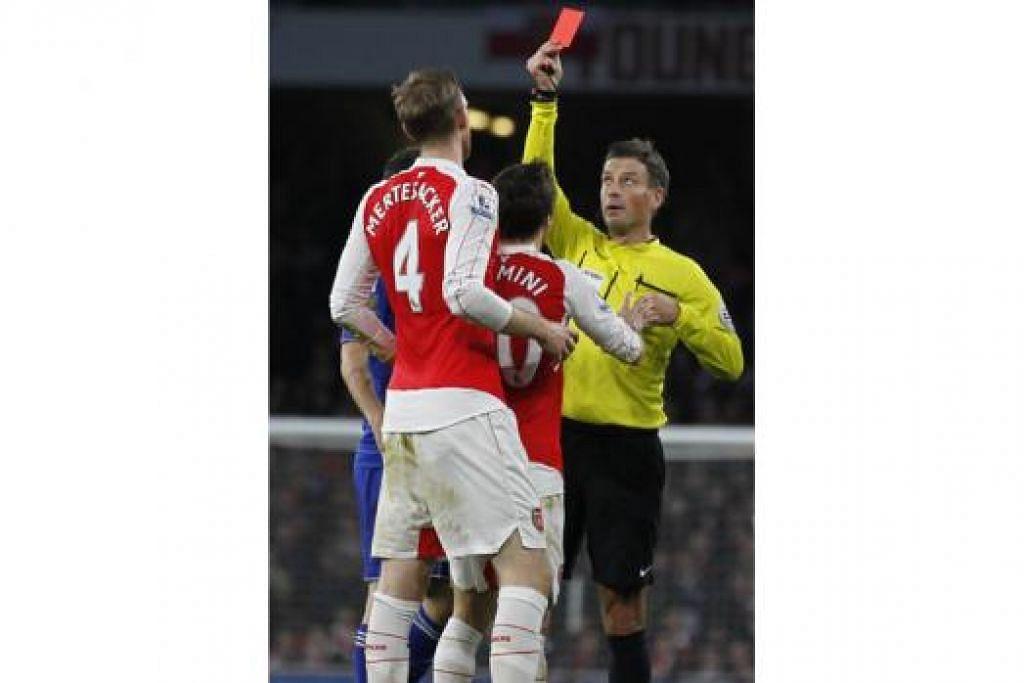 Pengadil Mark Clattenburg (kanan) melayangkan kad merah kepada pemain barisan pertahanan Arsenal, Per Mertesacker (kiri), dalam perlawanan tersebut. - Foto REUTERS dan AFP