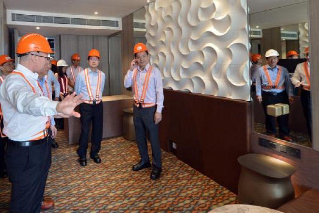 BILIK HOTEL PASANG SIAP: Encik Wong (kanan) memeriksa ruang di bilik pasang siap dalam peluasan Hotel Crowne Plaza Changi Airport semasa mengunjungi tapak binaan itu semalam. - Foto THE STRAITS TIMES