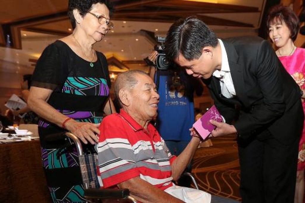 BERI HABUAN: Encik Chan memberi hong bao kepada mantan ketua jurutera marin dan anggota SMOU, Encik Leo Boon Hui (duduk), yang ditemani isterinya, Cik Dan Wah Eng (kiri), di majlis semalam. - Foto THE STRAITS TIMES