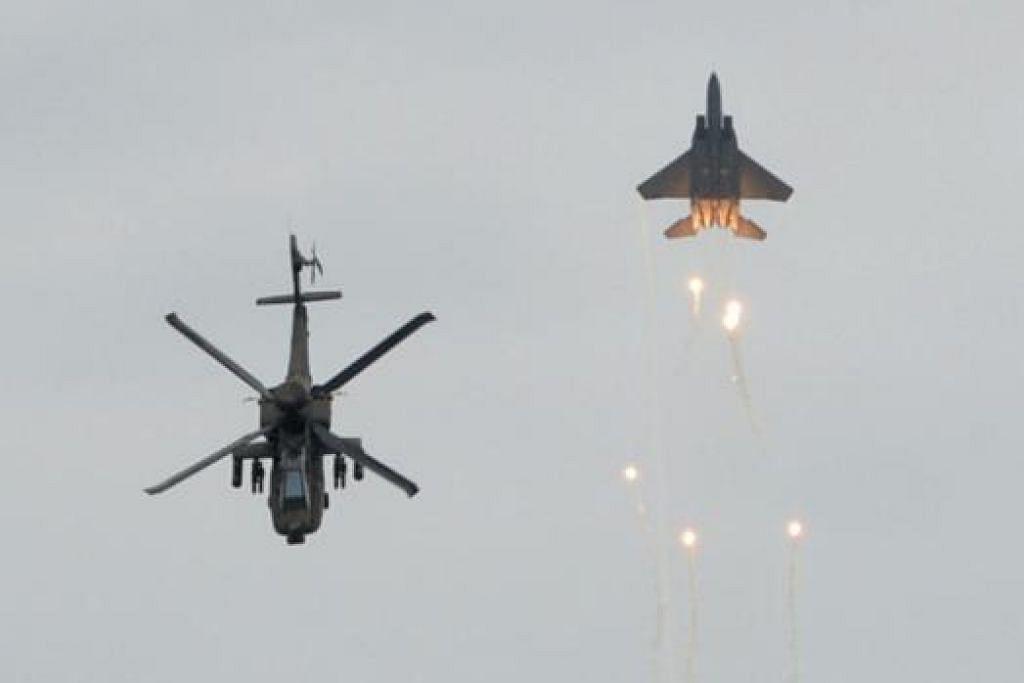 PERTUNJUKAN MEMUKAU: Helikopter AH-64D membuat gerakan seolah-olah memberi tabik bersama jet pejuang F-15SG.