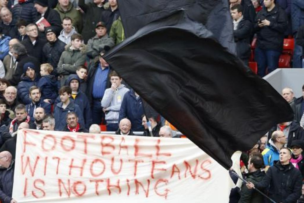 SUARA PENYOKONG: Sebahagian penyokong Liverpool mengibarkan bendera hitam dan sepanduk sebelum meninggalkan stadium pada minit ke-77 minggu lalu, sebagai membantah rancangan pemilik kelab menaikkan harga tiket musim depan. - Foto REUTERS