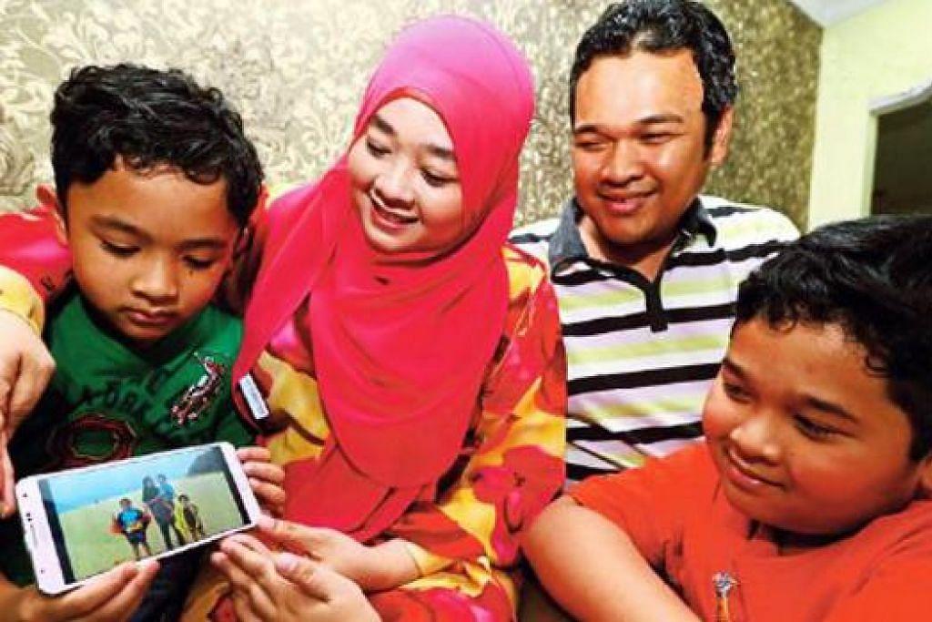 PERNAH ADA PEMBANTU RUMAH KEMBOJA: Cik Ida Adiba bersama keluarganya menatap gambar kenangan bersama bekas pembantu rumah mereka dari Kemboja. - Foto HARIAN METRO
