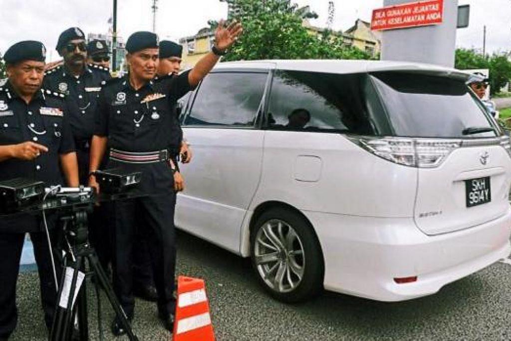 LAKSANA OPERASI: ACP Osman (kiri) menggunakan alat pengimbas nombor plat kenderaan automatik sewaktu Ops Saman Tertunggak sepanjang Jalan Johor Baru-Kota Tinggi kelmarin. Mesin itu akan mula dikerahkan di Bangunan CIQ Iskandar minggu depan. - Foto THE STAR