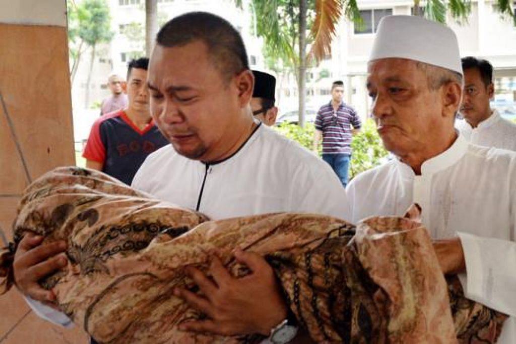 DAKAPAN TERAKHIR: Encik Syahrim tidak dapat menahan air mata sambil mendakap jenazah anak bongsunya yang meninggal dunia selang hampir sebulan selepas Allahyarhamha terjatuh daripada flat. - Foto M.O. SALLEH