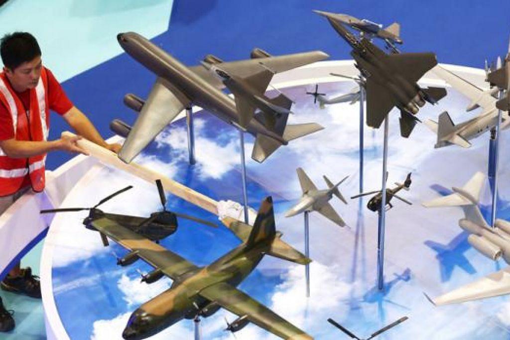 MEMASTIKAN SEMUA KEMAS DAN TERATUR: Seorang pekerja membersihkan model pesawat yang dipamerkan di kawasan pameran.