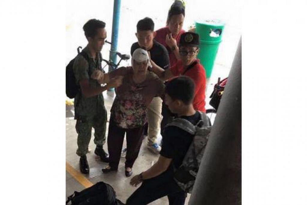 BERBAKTI TAK KIRA MASA, TEMPAT: 3SG Fahmi (berpakaian seragam) dan 3SG Mohammad Zulfadli (topi hitam) membantu wanita yang cedera akibat terjatuh dekat stesen MRT Yishun ke ambulans. - Foto ASHRAF ALI KHAN