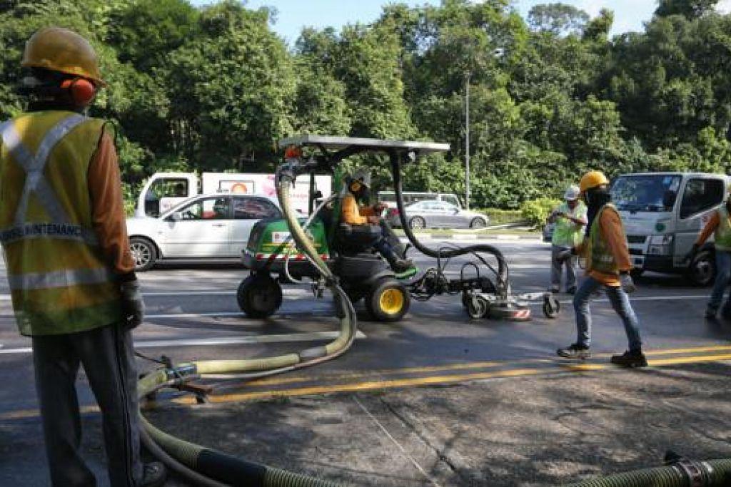 TUMPAHAN MINYAK KEEMPAT: Pekerja dilihat sedang membershikan minyak yang tumpah di Lornie Road ke arah Adam Road pagi semalam. - Foto THE STRAITS TIMES