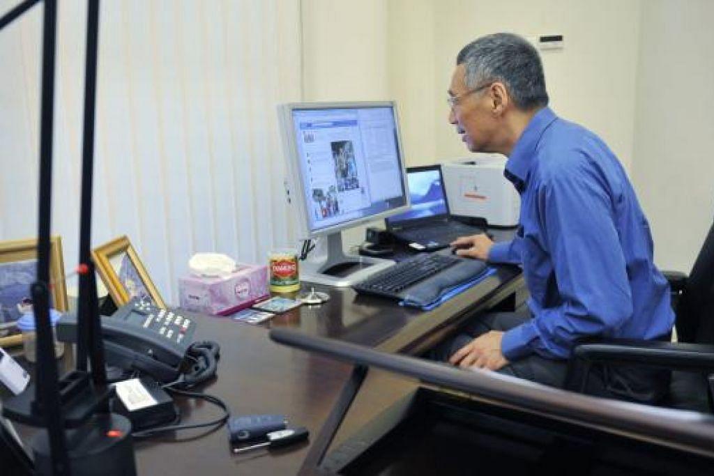 """Gambar tahun 2012 menunjukkan Perdana Menteri Lee Hsien Loong memeriksa halaman Facebook beliau di pejabat. Encik Lee memuat naik pos Facebook sulungnya pada 20 April 2012, apabila beliau melahirkan harapan rakyat Singapura akan mendapati laman beliau """"menarik"""". Gambar fail ST"""