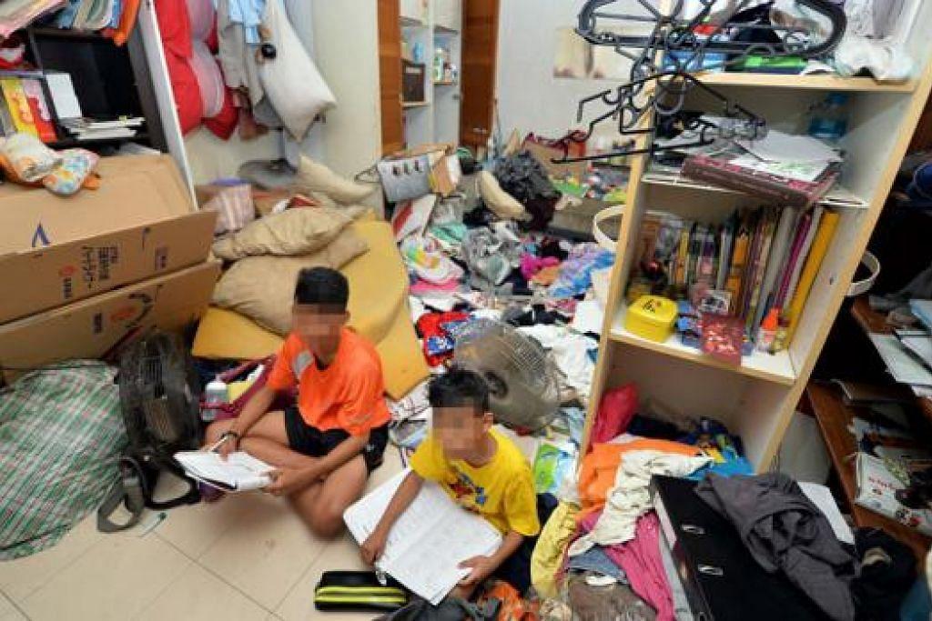 SELAGI MASIH ADA RUANG: Muhammad (kiri) dan adiknya yang hanya dikenali sebagai Zul menggunakan ruang kecil bersih bagi mengulang kaji pelajaran dan melakukan tugasan sekolah. - Foto M.O. SALLEH