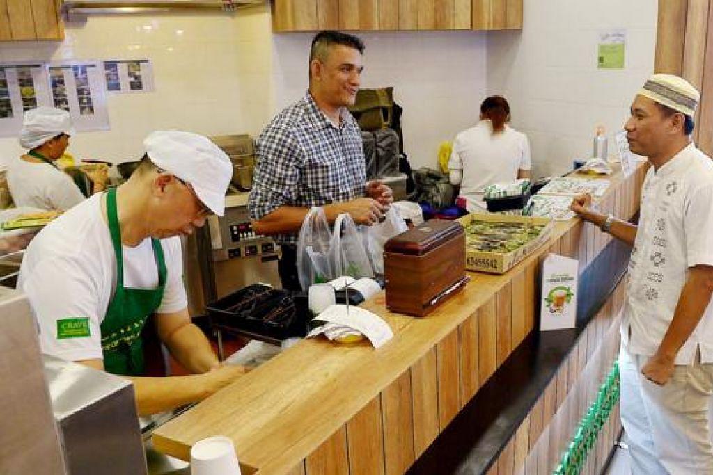 SELIA MUTU: Biarpun konsep gerai nasi lemak Crave di Bedok Mall berbeza daripada gerai di pusat penjaja di Adam Road, Encik Abdul Malik (berbaju kotak-kotak), yang sedang melayan seorang pelanggan, tetap memastikan mutu nasi lemaknya tetap sama dan bermutu.