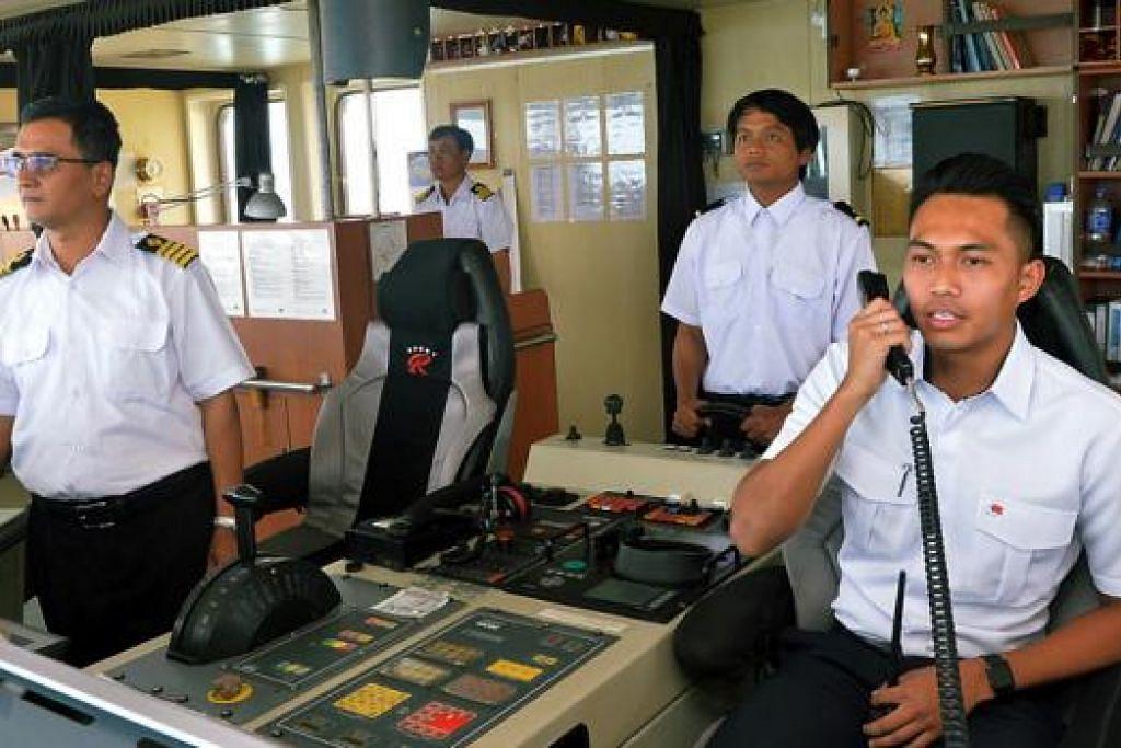 JALANKAN TUGAS DENGAN YAKIN DAN TENANG: Encik Zulhadis (kanan) semasa memberi arahan kepada nakhoda dan kru kapal supaya mereka dapat mengemudi kapal di perairan Singapura dengan baik.