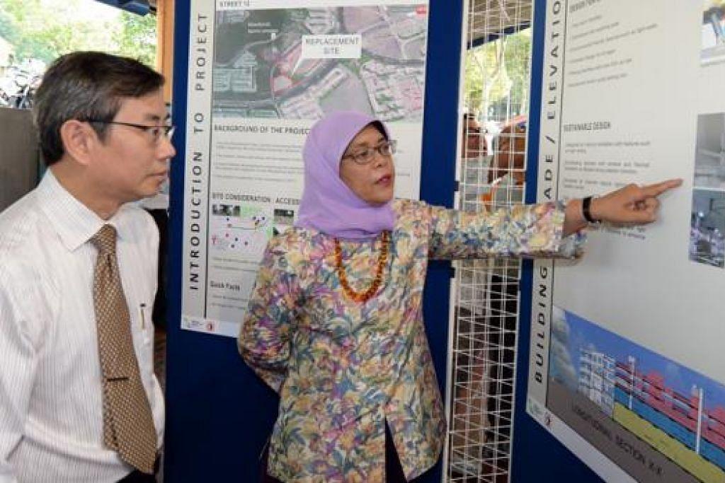 PROJEK SUNTIK NAFAS BARU: Cik Halimah bersama arkitek Encik Steven Chen memantau rancangan bagi projek pembangunan bersepadu yang merangkumi sebuah pusat penjaja, kedai dan pasar raya di Marsiling. - Foto ZAINAL YAHYA