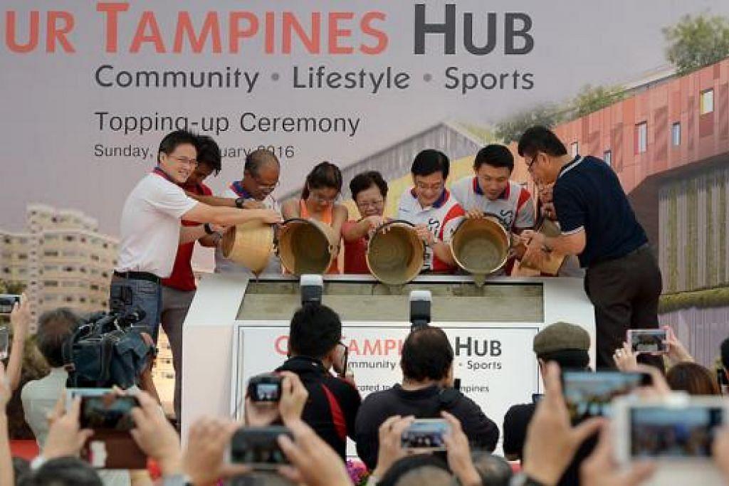 SIAP TAHUN INI: AP GRC Tampines Encik Choo (kiri), Encik Masagos (tiga dari kiri), Encik Heng (tiga dari kanan), Encik Baey (dua dari kanan) dan Cik Cheng (terlindung) di upacara untuk menandakan kemajuan dalam pembinaan projek Hab Bandar Tampines, semalam. - Foto TUKIMAN WARJI