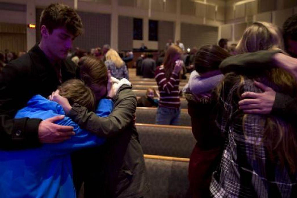 PILU ATAS KEMATIAN: Saudara-mara dan sahabat handai mangsa tembakan di Kalamazoo, Michigan, berkumpul, berdoa dan saling berpelukan di Gereja Center Point. - Foto AFP