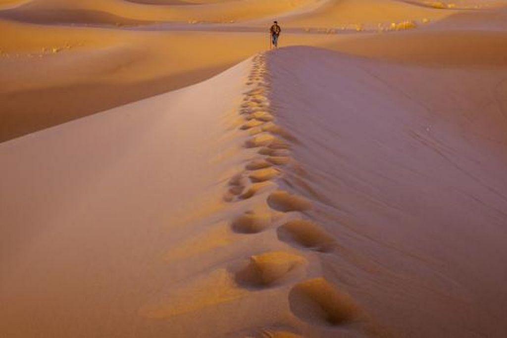 MENGENAL DIRI DALAM SUASANA ASING: Setiap kembara Encik Muhammad Noor Iskandar Othman ke negara eksotik mendekatkannya dengan proses mengenali diri dalam suasana yang asing, seperti foto seorang lelaki yang berjalan seorang diri di bukit pasir sekitar Yazd, Iran (gambar), yang dirakam beliau sebagai gambaran seseorang yang sedang mencari ketenangan dan keinsafan diri tanpa ditemani sesiapa, kecuali Tuhan. - Foto ihsan MUHAMMAD NOOR ISKANDAR OTHMAN
