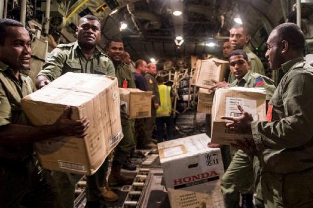 AGIHKAN BANTUAN: Bekalan bantuan termasuk alat jana kuasa, bekalan makanan dan minuman dibawa keluar tentera Fiji daripada sebuah pesawat C-130 milik Tentera Udara Diraja New Zealand. - Foto REUTERS