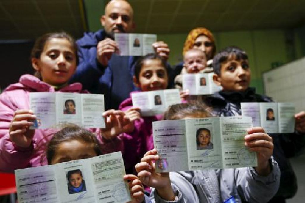 LARI DARIPADA PEPERANGAN: Keluarga pelarian dari Syria yang terus bergelora dengan perang saudara menunjukkan dokumen pendaftaran Jerman yang baru mereka terima di pusat pemeriksaan Herford. - Foto REUTERS