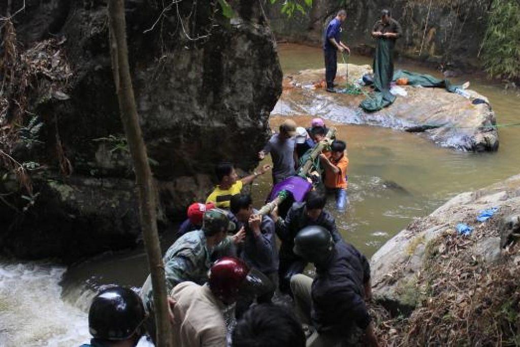 MAYAT DITEMUI: Pasukan penyelamat Vietnam terpaksa menuruni air terjun curam, sedang mengangkat tiga mayat pelancong Britain yang ditemui di kawasan air terjun di Dalat, yang popular di kalangan pelancong itu. - Foto AFP
