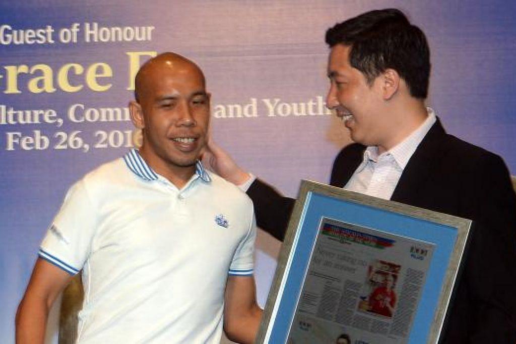 KECEMERLANGAN DIIKTIRAF: Kapten pasukan bola sepak Celebral Palsy Singapura, Khairul Anwar Kamsani (kiri), menerima cenderahati daripada Editor Sukan akhbar 'The Straits Times', Encik Marc Lim, di majlis anugerah kelmarin. - Foto TAUFIK A. KADER