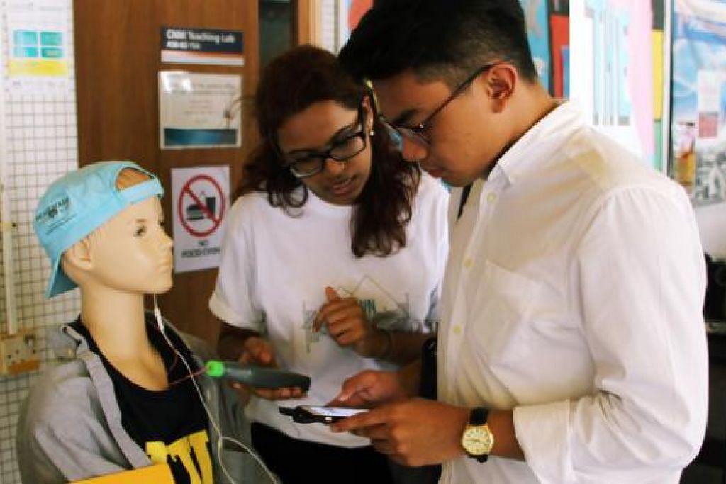 UJI TAHAP BUNYI: Mahasiswa NTU, Cik Navina Rajan menunjukkan seorang penuntut (kanan) bagaimana patung manusia boleh digunakan untuk menguji tahap bunyi alat pendengaran peribadi. Ia diadakan di pertunjukan kempen Down The Sound baru-baru ini.