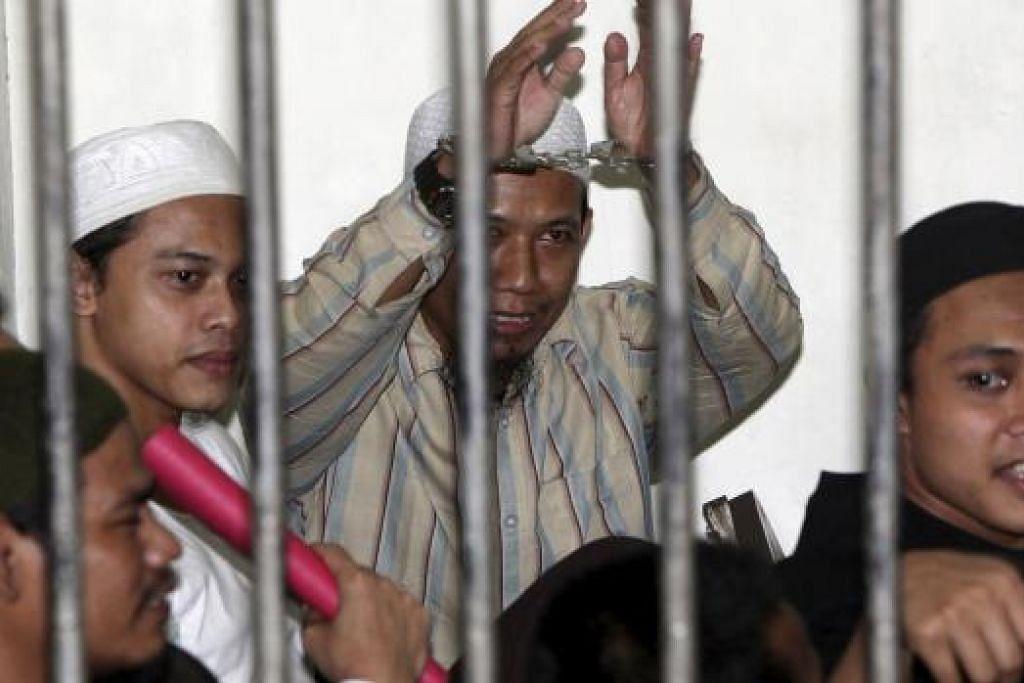 Perisikan Indonesia mengesan panggilan telefon dibuat dari penjara keselamatan maksimum Nusakambangan, tempat pengganas Aman Abdurrahman (tangan di gari dalam gambar atas) dan Iwan Darmawan Muntho  sedang menjalani hukuman penjara, ke Raqqa. kubu kuat ISIS di Syria. Gambar Reuters