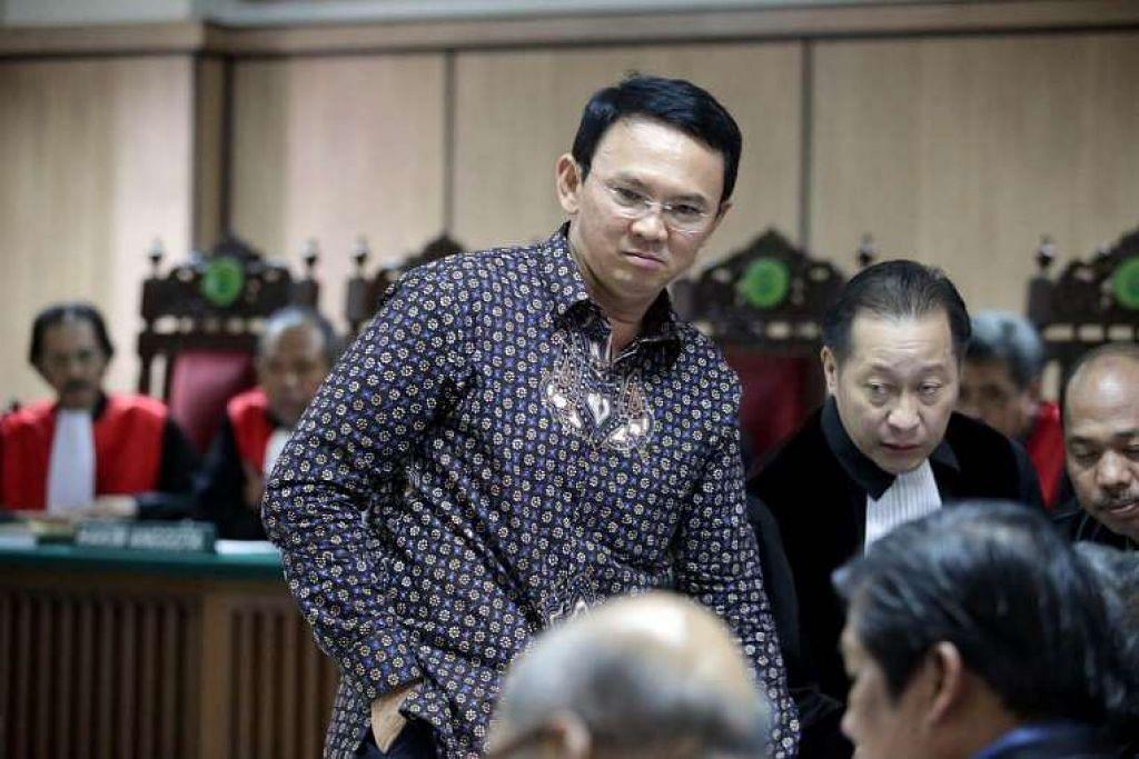 Gabenor Jakarta, Encik Basuki Tjahaja Purnama (tengah), bercakap dengan peguamnya dalam mahkamah semasa perbicaraan pada 27 Dis 2016.