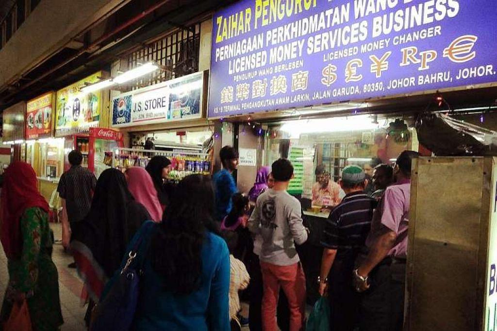 Kedai pengurup di Larkin, Johor, dipenuhi pelanggan. Salah satu sebab ringgit diramal jatuh lagi ialah ia dipengaruhi mata wang yuan China, yang akan kekal di bawah tekanan, menurut firma analisis pasaran BMI Research.