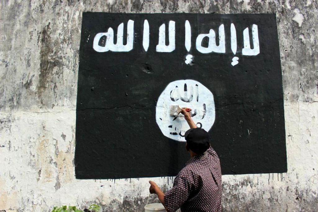 Seorang penduduk memadamkan contengan bendera ISIS di Solo, Jawa Tengah.